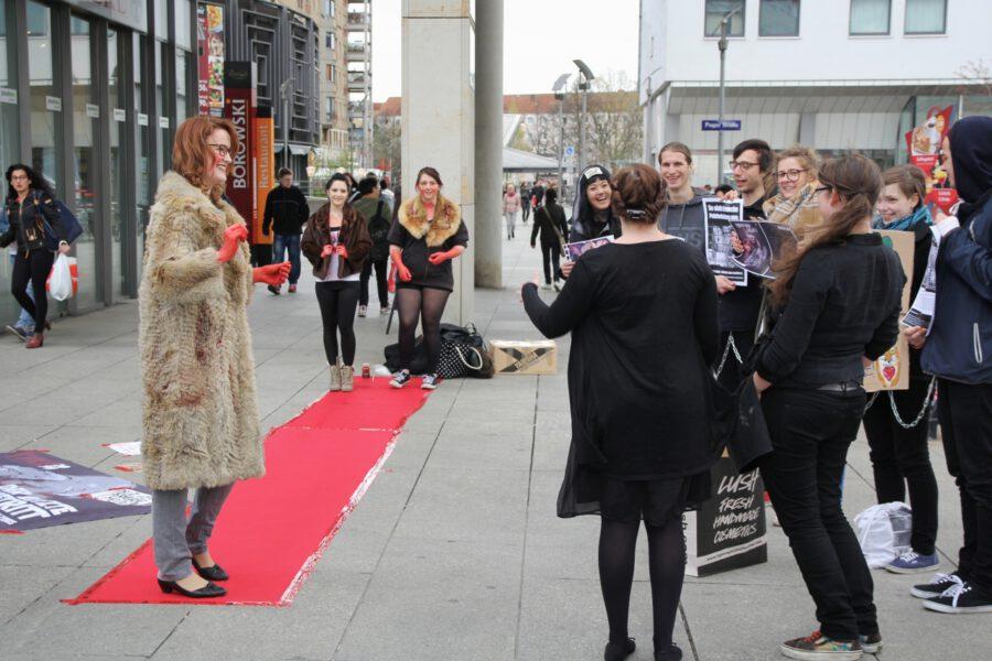 blutbeschmierte und Pelz tragende Models laufen über einen roten Teppich auf der Prager Straße