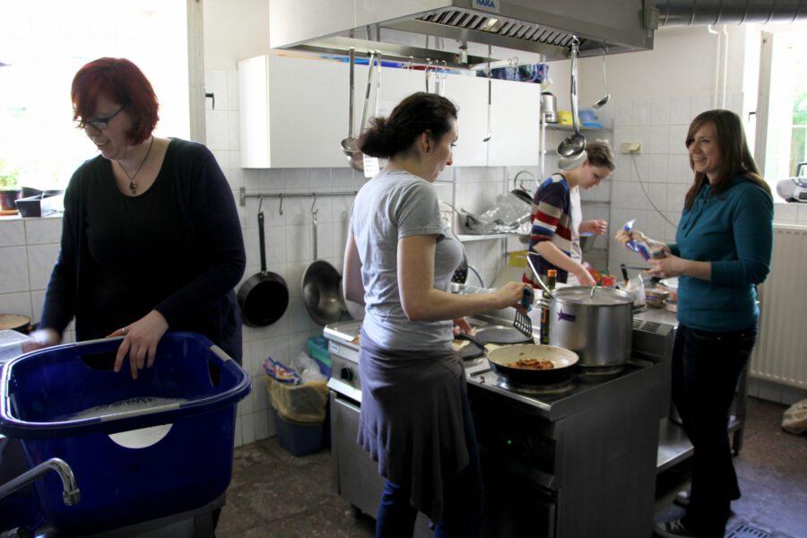 Mitglieder des Anima e.V. arbeiten fröhlich in der Küche