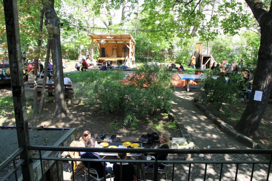 Brunch-Gäste sitzen überall im Garten verstreut und essen