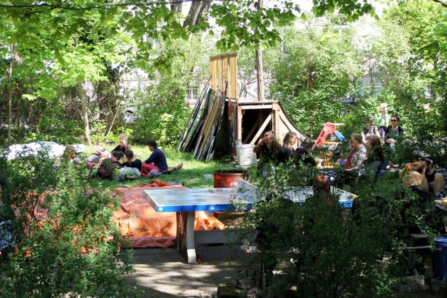 Gäste sitzen auf Decken und Stühlen in der Sonne