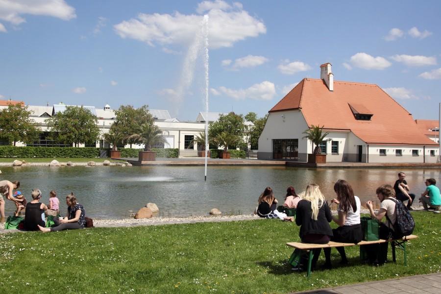 viele Menschen in der Sonne am See vor der Messehalle
