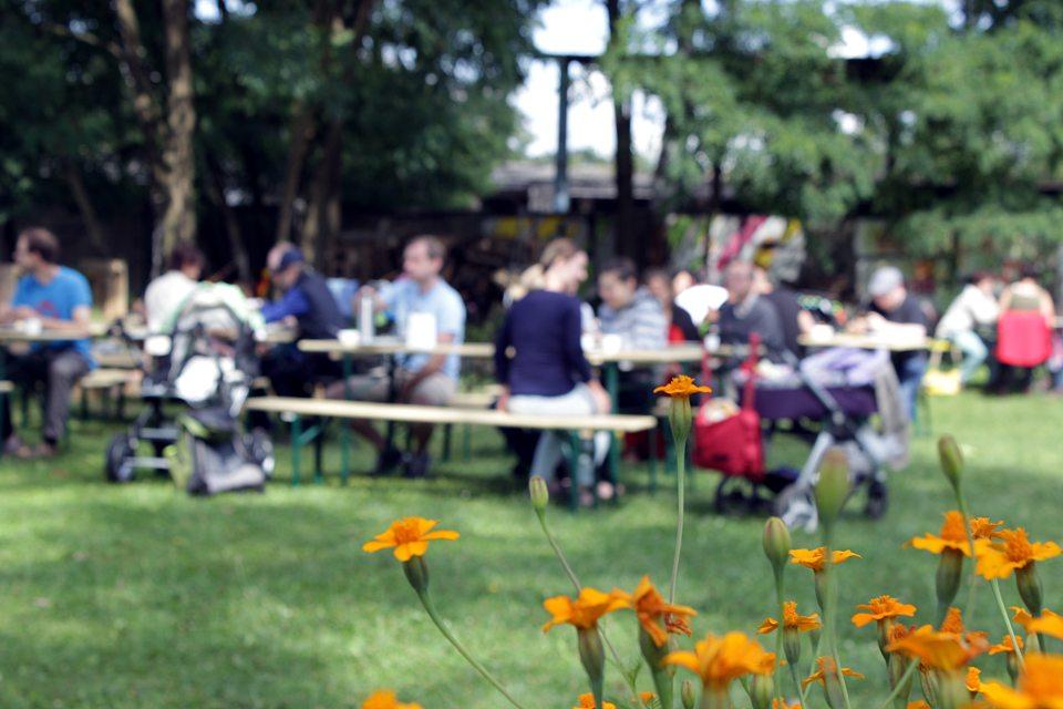 Brunchgäste sitzen auf Bänken im Golgi Park.