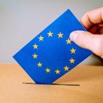 Ein Umschlag mit den Europasternen darauf wird in eine Wahlurne gesteckt