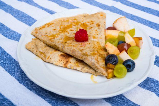 Crêpe auf einem Teller, dekoriert mit frischem Obst.