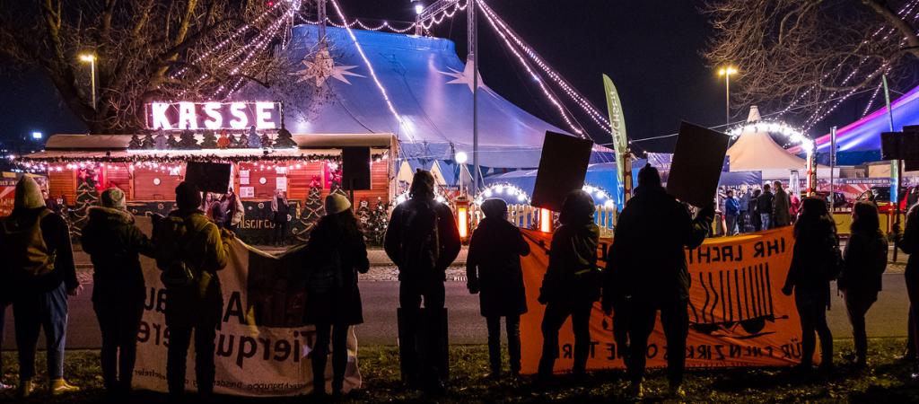 Menschen mit Schildern vor einem Zirkus