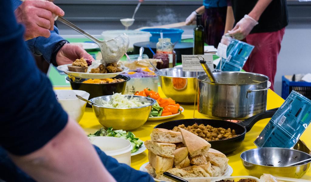 Eine Theke mit veganem Essen, u.a. Soja-Gyros, Tsatsiki und Fladenbrot.