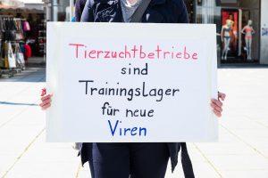 """Ein Schild mit der Aufschrift """"Tierzuchtbetriebe sind Trainingslager für neue Viren"""""""