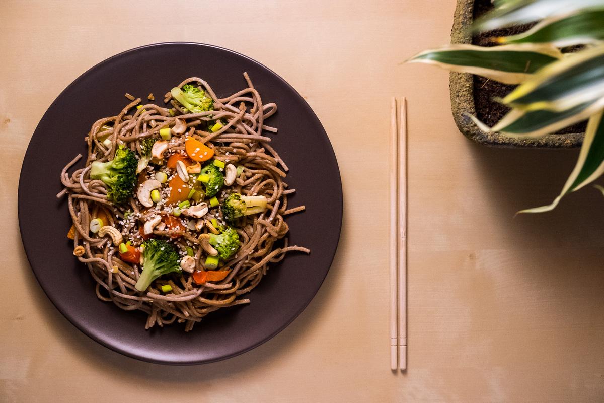 Spicy Garlic Soba Noodles auf einem Teller mit Essstäbchen daneben
