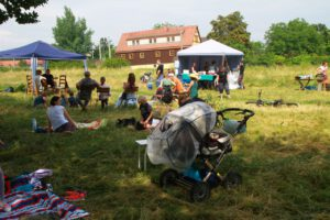Ein Zelt mit Menschen im Hintergrtund, sowie Menschen, die ein Picknick zwischen hohen Gräsern machen