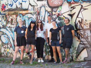 Bild mit einer Gruppe von Menschen, du vor einer Wand mit Graffitis stehen.